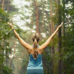 Woman standing in nature with arms outstretched
